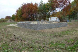 """Ściany fundamentowe muruje się przeważnie z bloczków betonowych na zaprawie cementowej – przy ocenie kosztów ich wykonania zapomina się często, że przed wykonaniem izolacji trzeba ich powierzchnię najpierw """"wyrapować"""""""