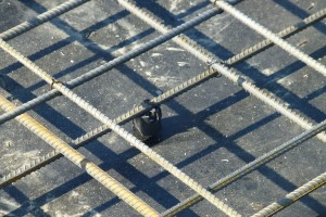 Plastikowe podkładki dystansowe, oddzielające dolne pręty od deskowania płyty żelbetowej, gwarantują odpowiednie otulenie zbrojenia betonem