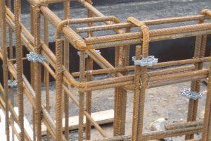 Okrągłe podkładki dystansowe, nakładane w różnych miejscach na pręty, zapewniają właściwe otulenie betonem zbrojenia belek i ścian żelbetowych