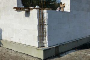 W miejscu, w którym zbrojenie słupa w zewnętrznej ścianie parteru jest zakotwione w ścianie fundamentowej nie wyrównujemy powierzchni betonu; nie układamy też w tym miejscu poziomej izolacji przeciwwilgociowej