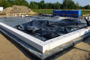 Nie doprowadzimy do przyspieszonej utraty wilgoci przez beton, a przez to do jego osłabienia, jeśli świeżo ułożoną płytę fundamentową będziemy przez kilka pierwszych dni polewać wodą i przykrywać folią