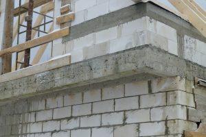 """Tutaj wykonawca nie był zbyt dużym fachowcem – na belce żelbetowej widać nie tylko """"raki"""" i przewarstwienia betonu, ale także korodujące już pręty, pozbawione betonowego otulenia"""
