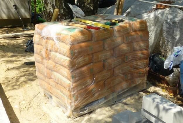 Jeśli cement jest przechowywany na wolnym powietrzu, to worki powinny zostać ułożone na drewnianej palecie i nie być pozostawiane bez przykrycia folią